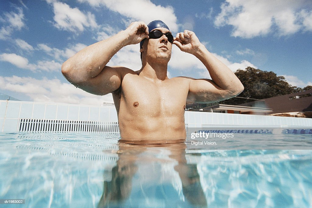 Young Man Standing in a Swimming Pool Adjusting His Swimming Goggles : Stock Photo