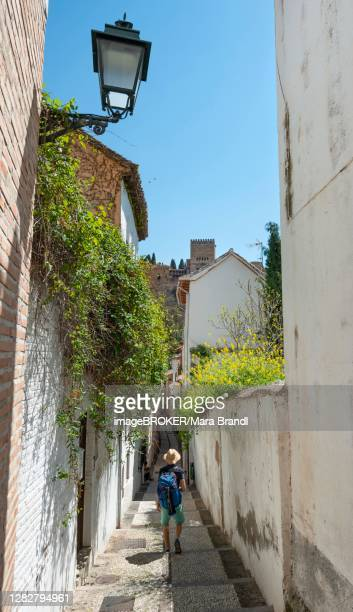 young man standing in an alley, view of the towers of the alhambra, albaicin district, granada, andalusia, spain - granada provincia de granada stock pictures, royalty-free photos & images