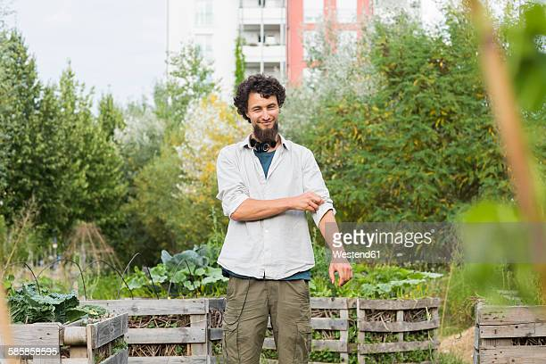 young man standing in an urban garden - rolled up sleeves stock pictures, royalty-free photos & images