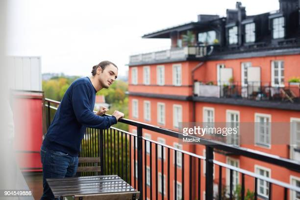 Young man standing in balcony at urban rental apartment