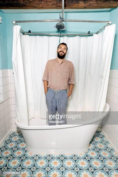 young man standing in bath tub, laughing - maenner duschen stock-fotos und bilder