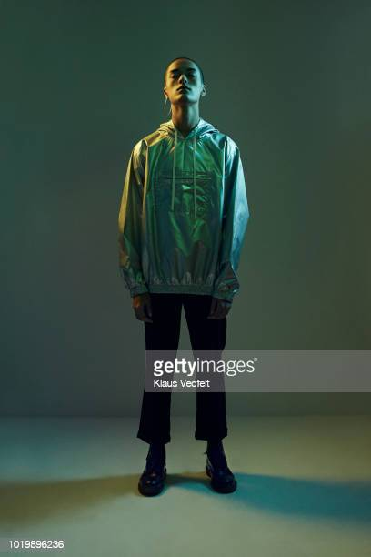 young man standing in coloured lights with closed eyes , shot on studio - encuadre de cuerpo entero fotografías e imágenes de stock