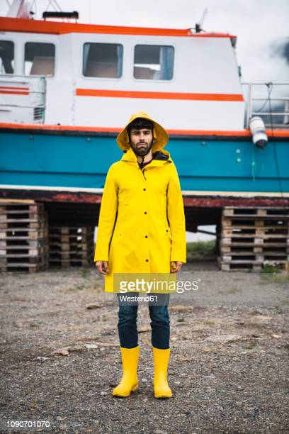 young man standing in front of a ship, wearing rain clothes, lapland, norway - rubber boot stock pictures, royalty-free photos & images