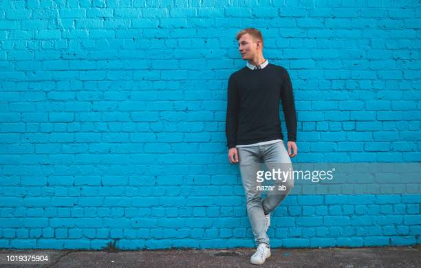 Young man standing in front of big teal blue wall.