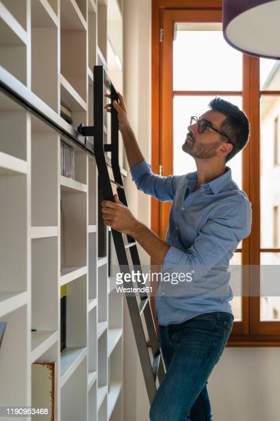 young man standing in front of bookshelves at home looking up - hellblau stock-fotos und bilder