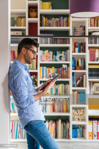 young man standing in front of bookshelves at home using digital tablet - hellblau stock-fotos und bilder