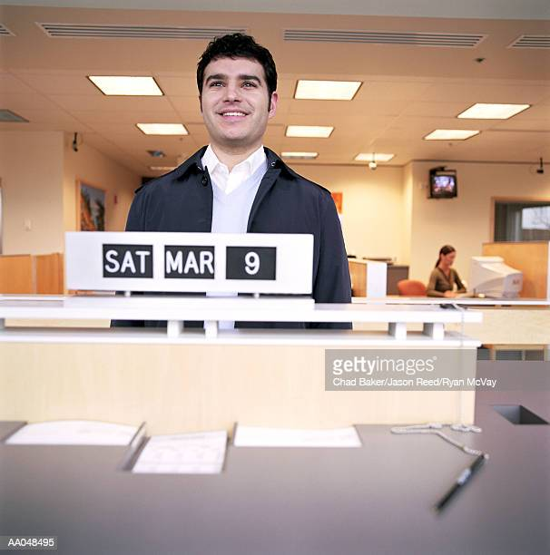Young man standing in front of calendar at bank counter, smiling