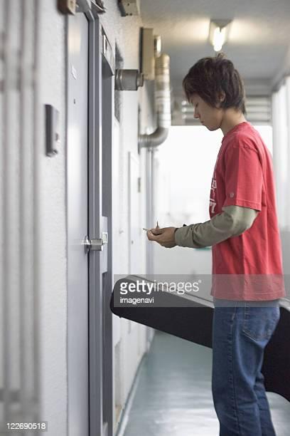 Young man standing in front of door