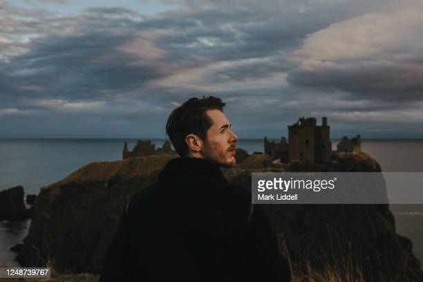 young man standing in front of dunnottar castle at sunset, scotland - dunnottar castle stock pictures, royalty-free photos & images