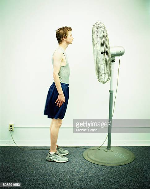 Young Man Standing in Front of Fan