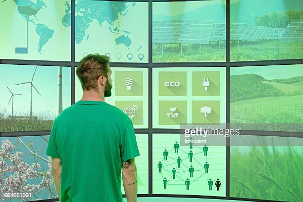 Young man standing in front of graphical screens showing environmental images, rear view