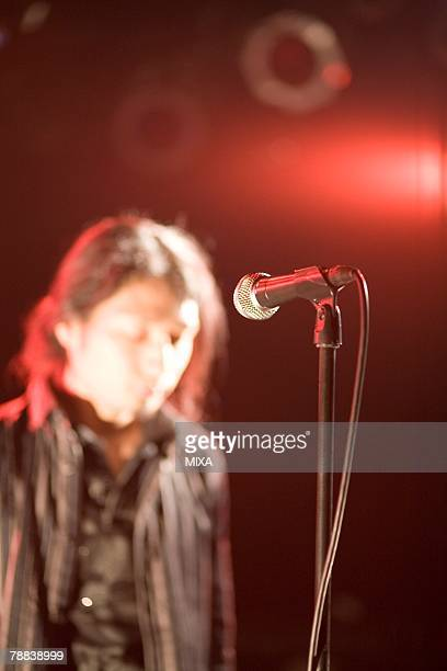 young man standing in front of microphone - modern rock stock pictures, royalty-free photos & images