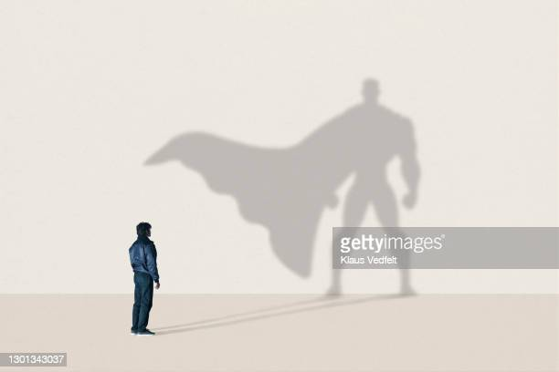 young man standing in front of superhero shadow - shadow stock pictures, royalty-free photos & images