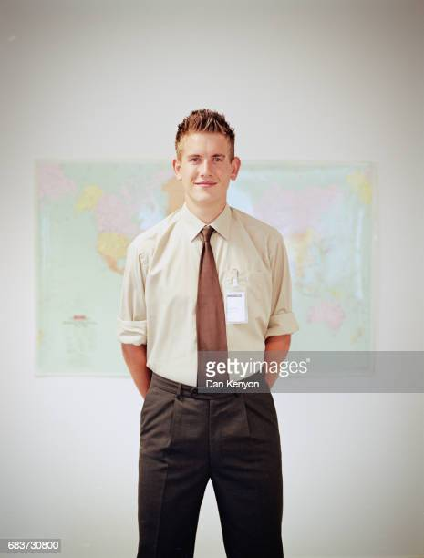 Young man standing in front of wall map with name badge on