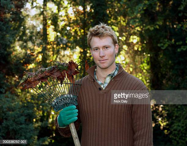 young man standing in garden holding rake, smiling, portrait - brown glove stock pictures, royalty-free photos & images