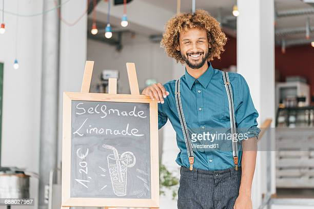 young man standing in his own coffee shop - サスペンダー ストックフォトと画像
