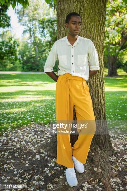 young man standing in park - pantalon photos et images de collection