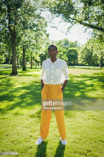 young man standing in park - hands in pockets stock pictures, royalty-free photos & images