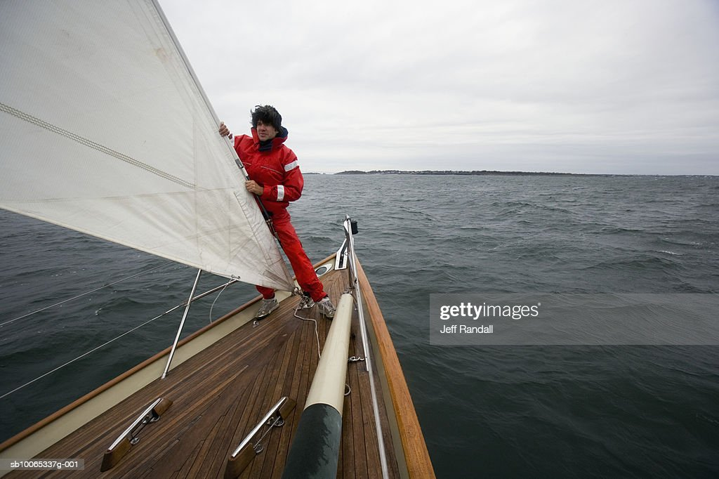 Young man standing in racing yacht : Foto stock
