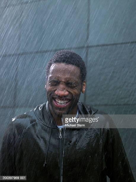 Young man standing in rain, eyes tightly closed, close-up