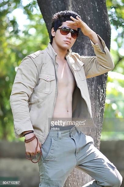 young man standing in shielding eyes position - hot indian model stock pictures, royalty-free photos & images