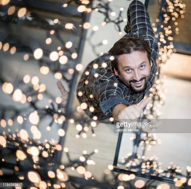 young man standing in shopping mall filled with lights - beautiful ramadan stock pictures, royalty-free photos & images
