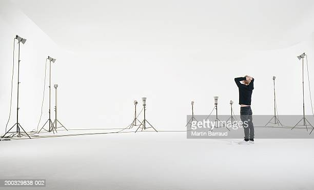 Young man standing in studio with lights set up, hands on head