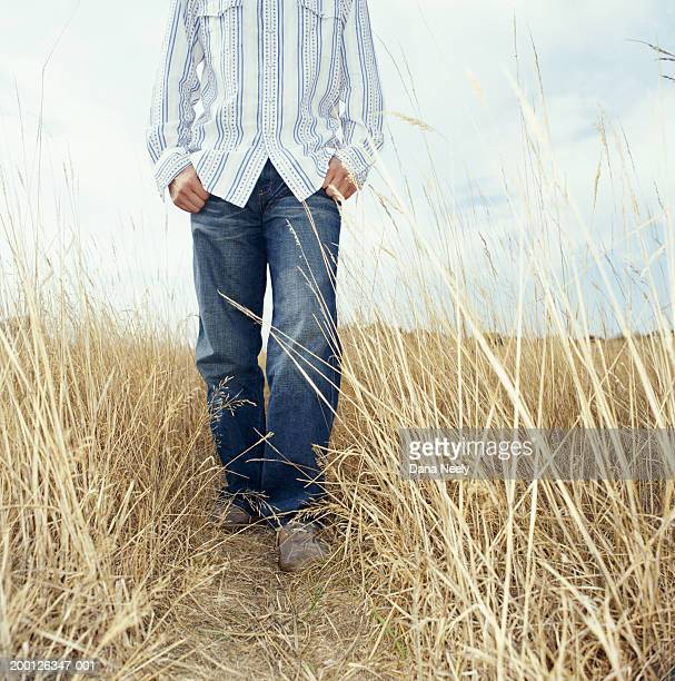 Young man standing in tall grass, low section