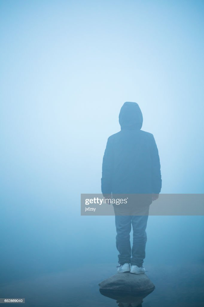 young man standing in the mist : Stock Photo