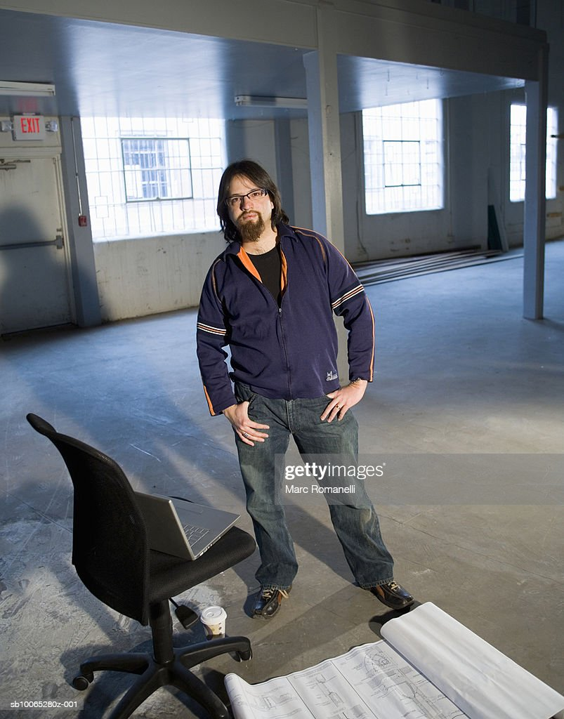 Young man standing in warehouse next to blueprints, portrait : Foto stock