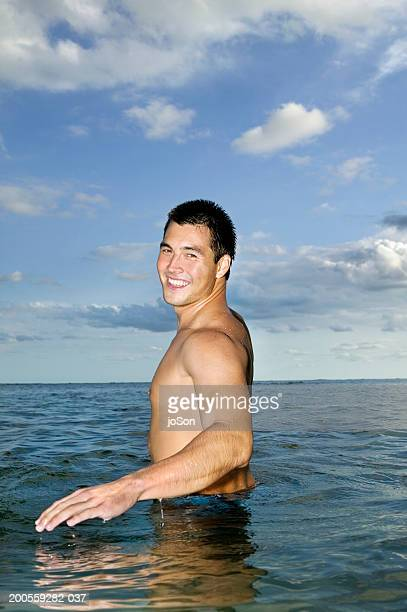 Young man standing in water, smiling, portrait