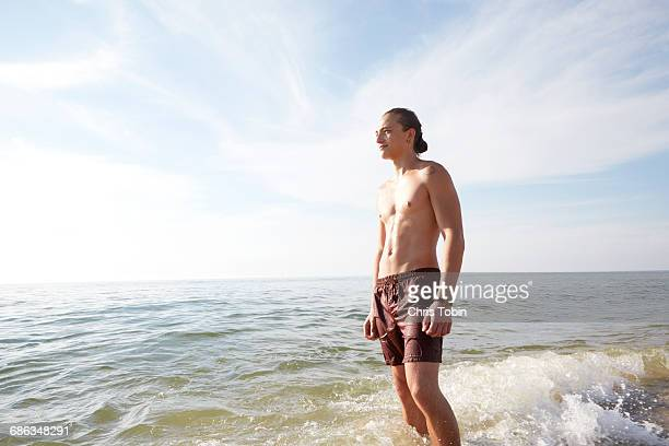 Young man standing in waves at beach