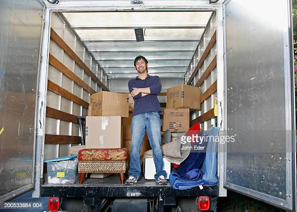 Young man standing inside moving van