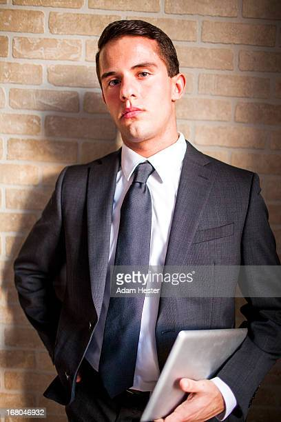 a young man standing inside with a tablet device. - only young men stock pictures, royalty-free photos & images