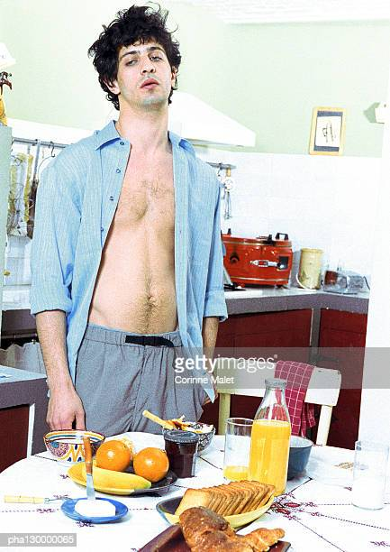 Young man standing near breakfast table.