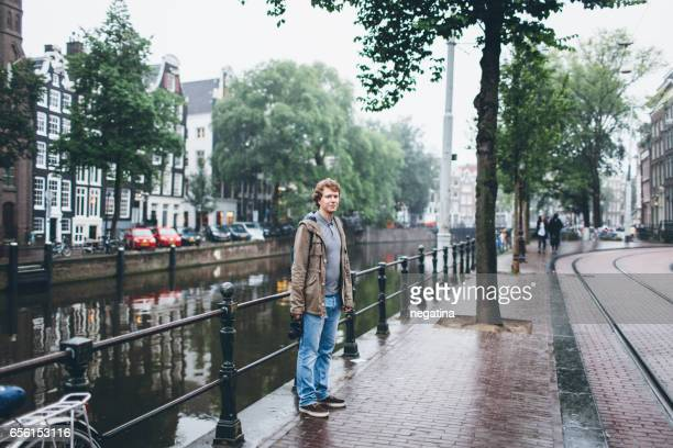 young man standing near canal in Amsterdam, Netherlands