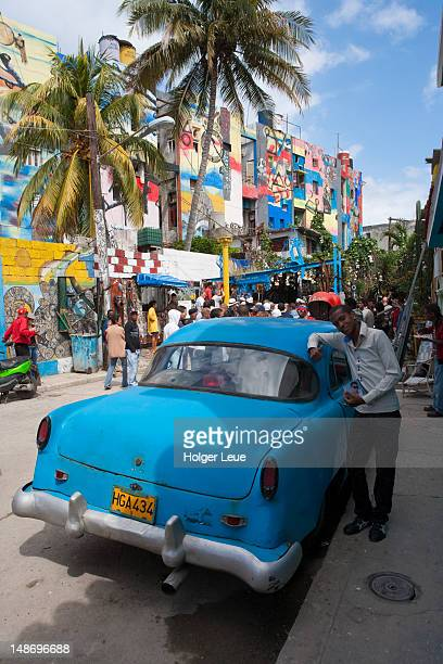 young man standing next to blue car at callejon de hamel with sunday afternoon rumba crowd in background. - callejon stock pictures, royalty-free photos & images