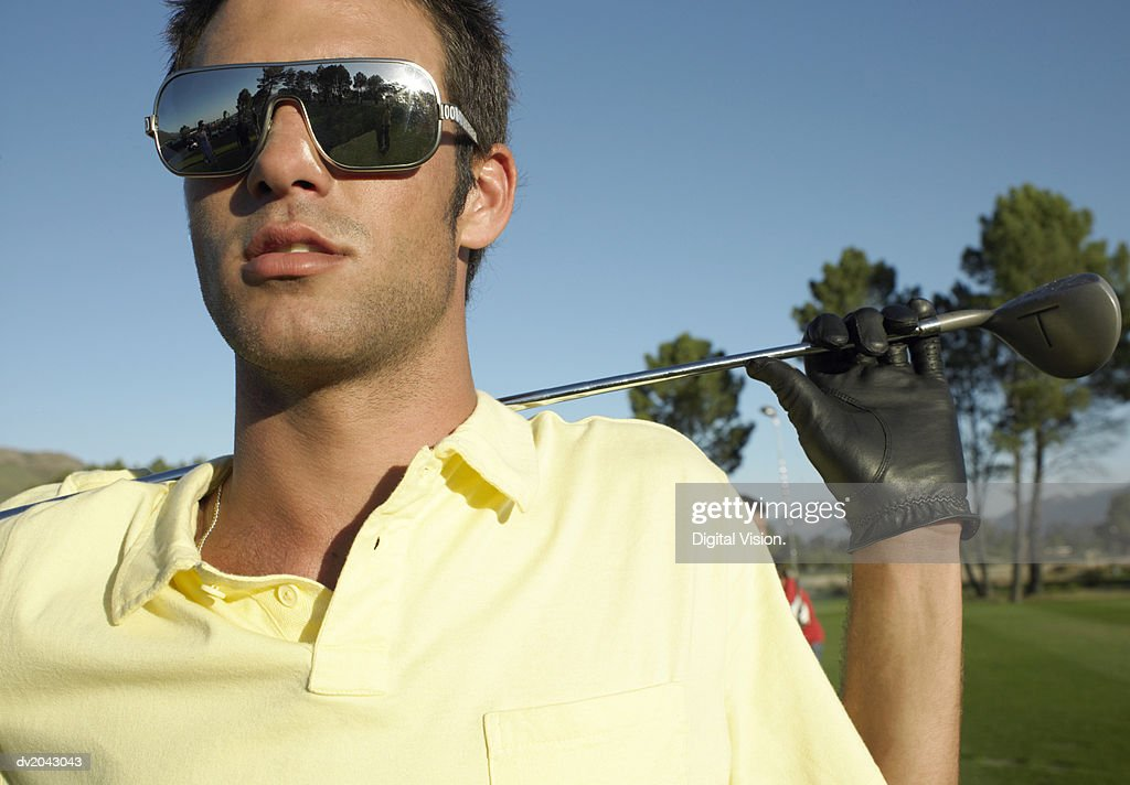 Young Man Standing on a Golf Course Wearing Sunglasses : Stock Photo