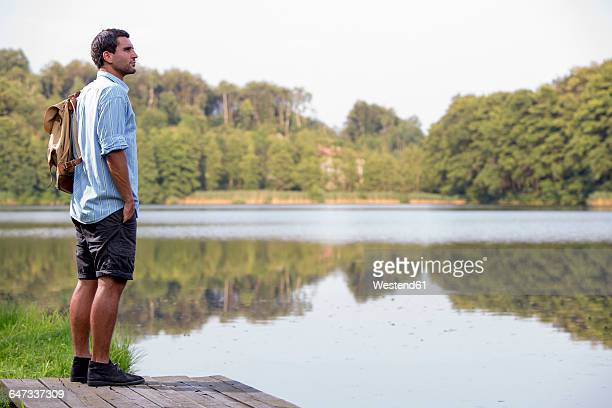 Young man standing on a jetty at lake looking at distance