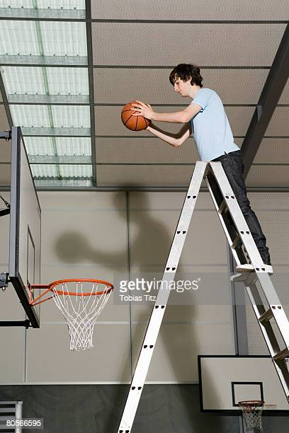 a young man standing on a ladder preparing to drop a basketball into a basketball hoop - making a basket scoring stock pictures, royalty-free photos & images