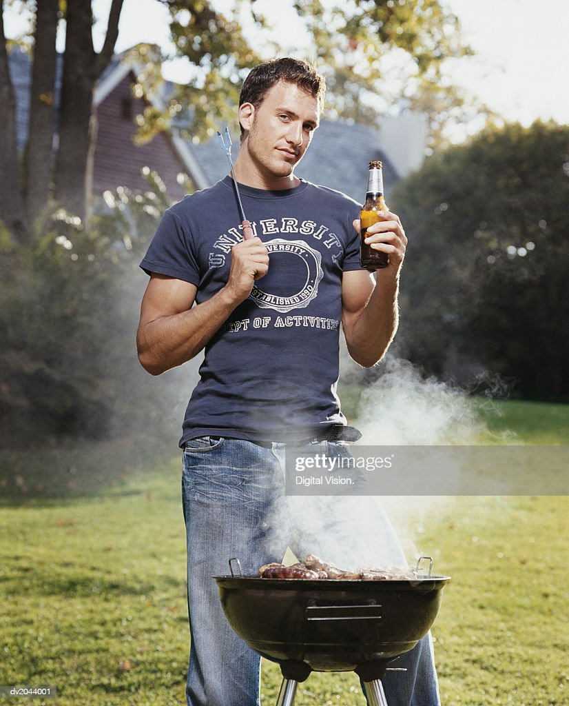 Young Man Standing on a Lawn With a Beer by a Barbecue : Stock Photo