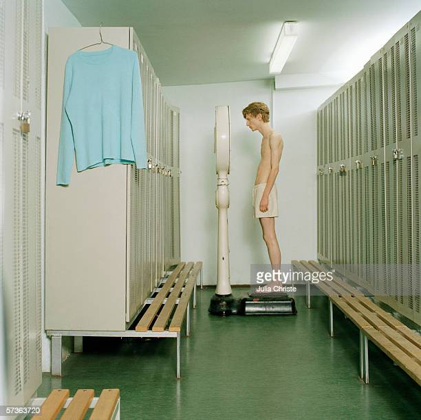 a young man standing on a scale in a locker room - delgado fotografías e imágenes de stock