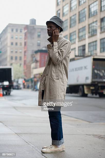 a young man standing on a sidewalk and using a mobile phone - トレンチコート ストックフォトと画像