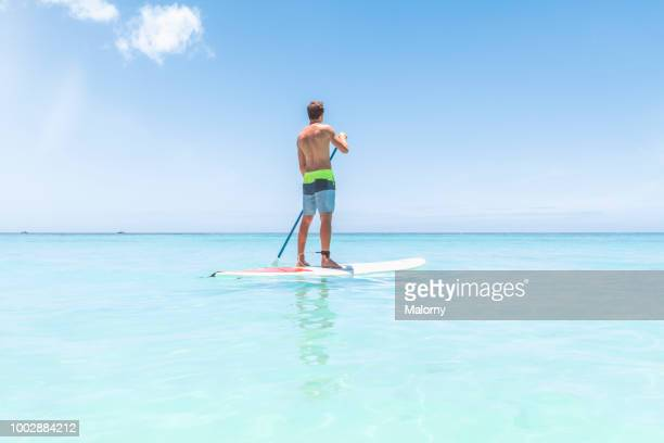 young man standing on a sup board or paddleboard, floating on the clear blue water, looking away. trou-aux-biches, pamplemousses district, mauritius. - islas mauricio fotografías e imágenes de stock