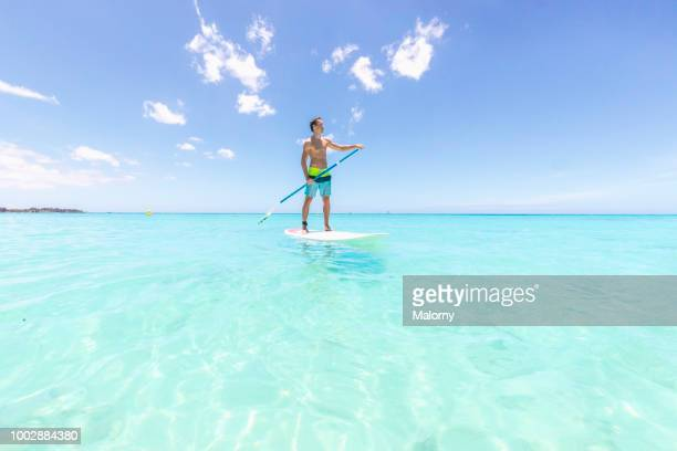 young man standing on a sup board or paddleboard, floating on the clear blue water, looking away. trou-aux-biches, pamplemousses district, mauritius. - ile maurice photos et images de collection