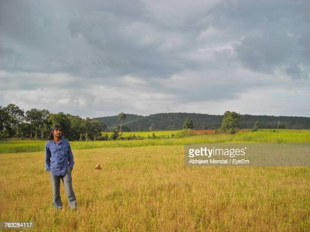 Young Man Standing On Agricultural Field Against Cloudy Sky