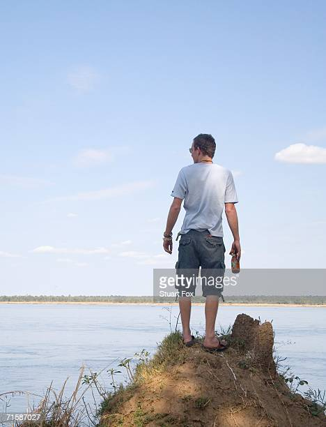 young man standing on an anthill overlooking the zambezi river - world at your fingertips stock pictures, royalty-free photos & images