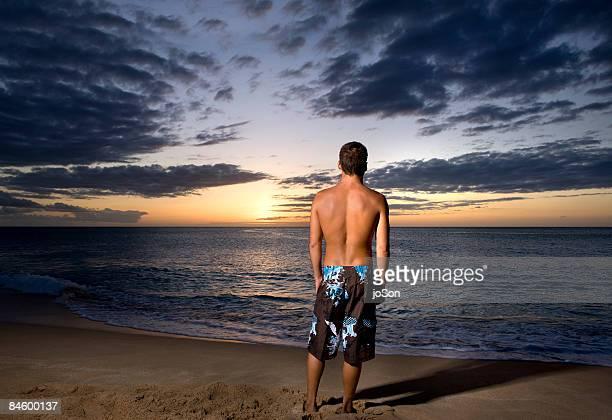 Young man standing on beach facing ocean