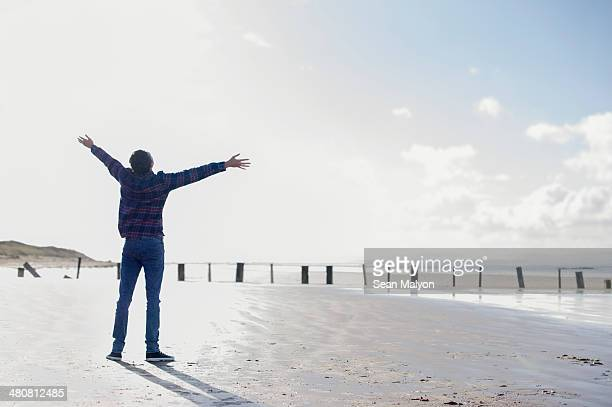 young man standing on beach with arms out, brean sands, somerset, england - sean malyon stock pictures, royalty-free photos & images