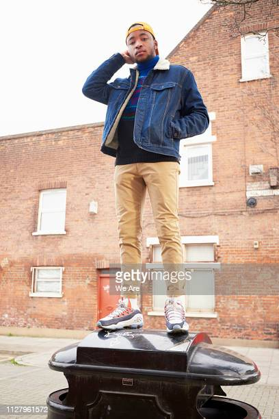 young man standing on bin in city street - khaki trousers stock pictures, royalty-free photos & images
